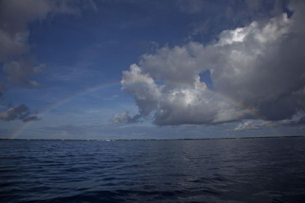 The island of Fongafale with Vaiaku visible under a rainbow across the lagoon | Villaggio di Vaiaku | Tuvalu