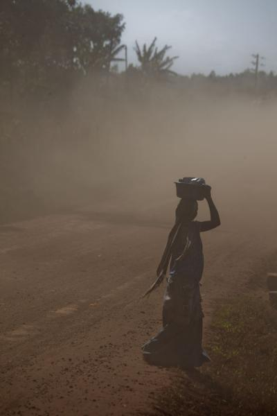 Woman braving the dust of the road from Jinja to Bujagali | Jinja | Uganda