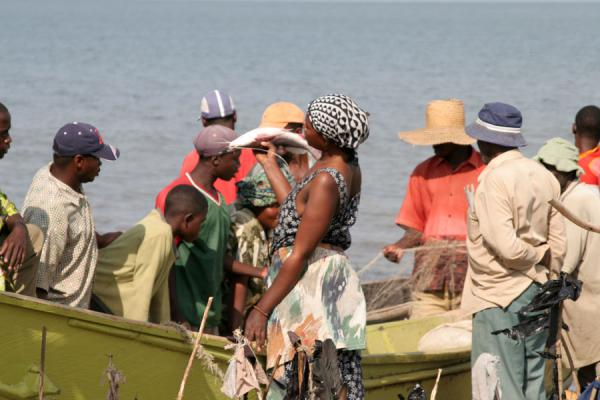 Woman trying to sell a fish at a fish market on Lake Edward | Uganda people | Uganda