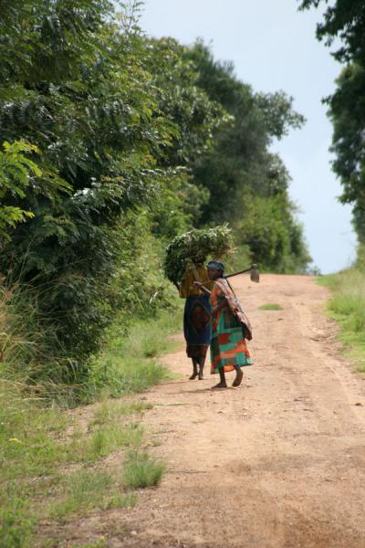 Women looking back while walking on the road | Uganda people | Uganda