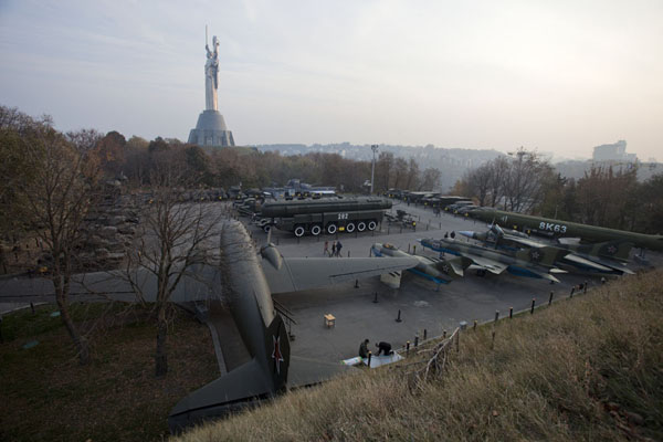 Overview of military arsenal of planes, tanks, and boats with Rodina Mat in the background | History of Great Patriotic War museum | Ukraine