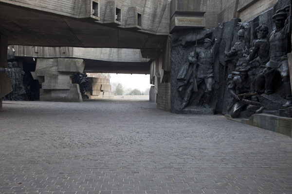 Picture of Soviet-style sculptures on the walls of a tunnel under the eternal flame, which is extinguished