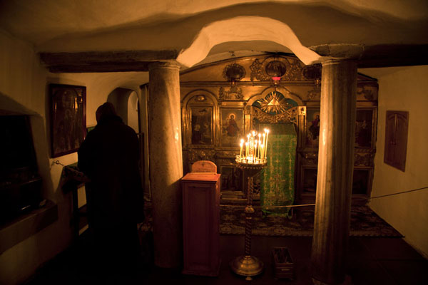 Old woman praying inside a small cavern in which a mummy is buried | Kyevo Pečerska Lavra | Ucraina