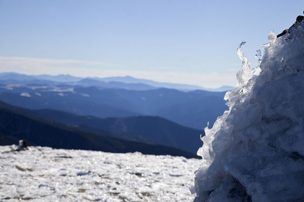 Icy view from the top of Mount Hoverla with ice-covered stone pillar in the foreground | Mount Hoverla | Ukraine
