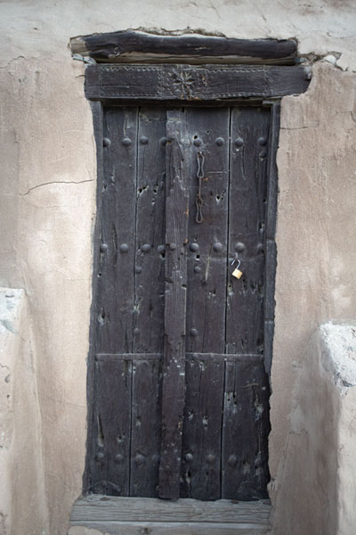 Carved wooden door in the defensive tower overlooking the fort | Forteresse de Al-Hayl | Emirats Arabes Unis