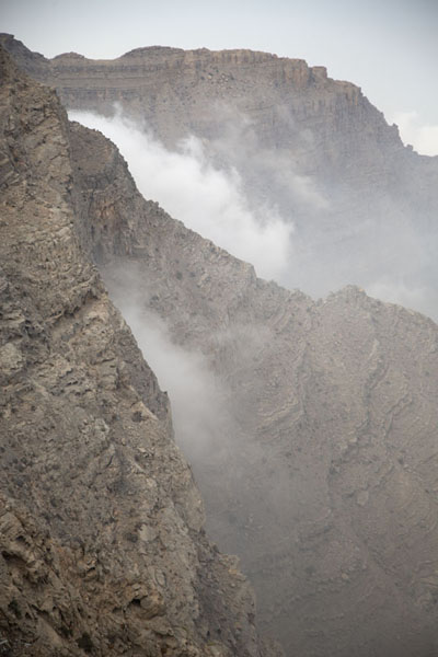 Foto van Clouds hanging against the steep mountain slopes of Jebel JaisJebel Jais - Verenigde Arabische Emiraten