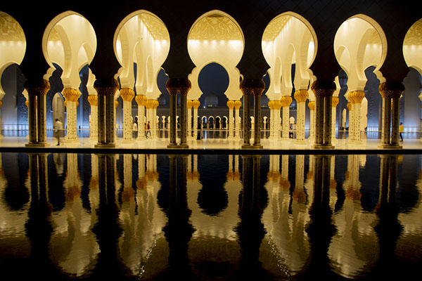 Evening view of the Grand Mosque with lighted arches reflected in a pool | Gran mezquita del Sheikh Zayed | Emiratos Arabes Unidos
