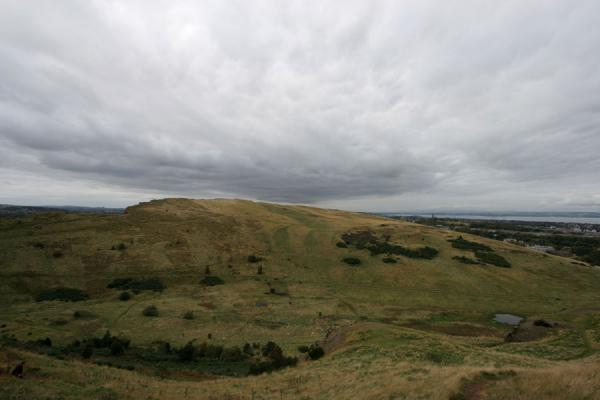 Foto di Green slopes of Arthur's Seat with grey skyEdimburgo - Regno Unito