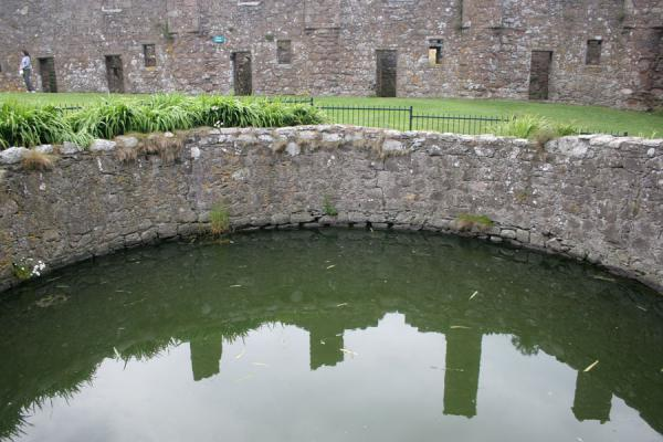 Watertank providing support during long sieges and reflection of houses | Dunnottar Castle | United Kingdom
