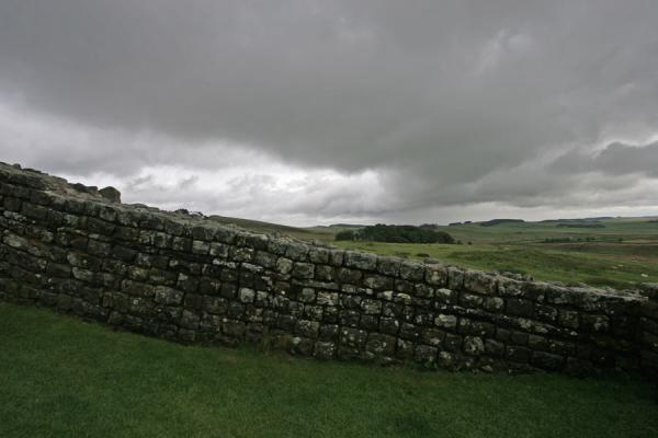 Wall of Vercovicium in green landscape and under dark clouds | Vercovicium Roman Fort | United Kingdom