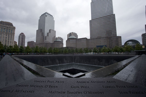 Picture of 9/11 Memorial (U.S.A.): North Pool with surrounding skyscrapers under a dark sky