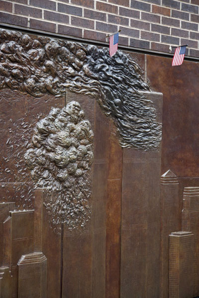 The burning World Trade Center towers sculpted in a wall close to the memorial | 9/11 Memorial | U.S.A.