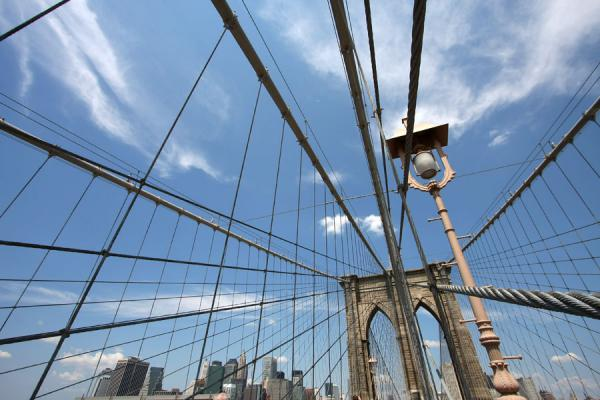 Picture of Brooklyn Bridge (U.S.A.): Pylon, street-lamp, cables and Manhattan in the background