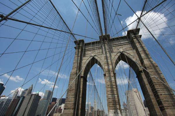 Picture of Brooklyn Bridge (U.S.A.): Gothic style pylon of Brooklyn Bridge with lower Manhattan in the background