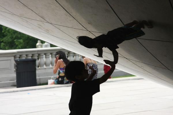 Boy playing with the distorted reflection of himself at the Bean | Chicago Millennium Park | U.S.A.