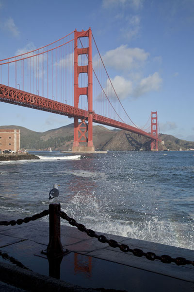 The Golden Gate Bridge with wave crashing against the quay on the south side | San Francisco | U.S.A.