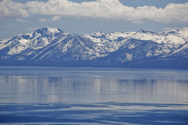 Snow-capped mountains reflected in the calm waters of Lake Tahoe | Lake Tahoe | United States