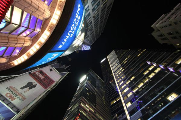 Looking up some of the brightly lit skyscrapers at Times Square | Times Square | Stati Uniti