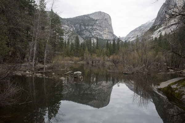 Mirror Lake reflecting surrounding mountains in its quiet waters | Yosemite landscapes | United States