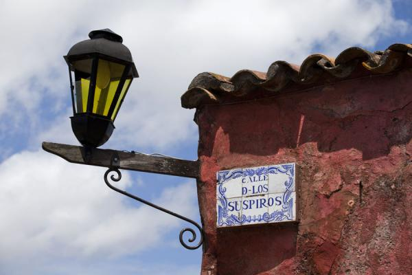 Foto de Detail of lantern and street sign at the corner of Calle de los SuspirosColonia del Sacramento - Uruguay