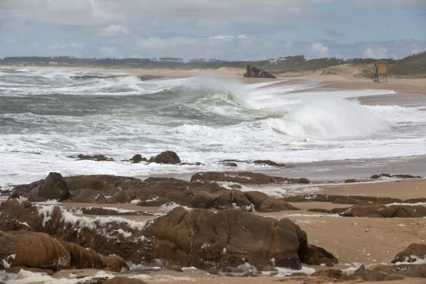 Foto de Waves on the beach of La Pedrera with rocks in the foreground - Uruguay - América
