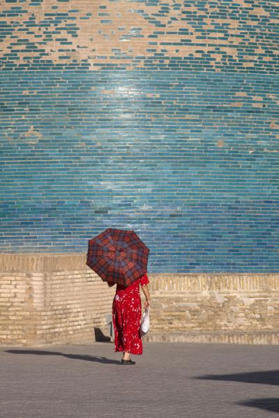 Picture of Khiva (Uzbekistan): Green, blue, and red: Kalta Minor with woman dressed in red