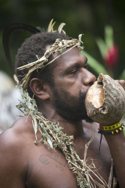 Blowing a conch shell at the end of one of the dances of the Big Namba's | Mae Big Namba's | St Vincent en de Grenadines