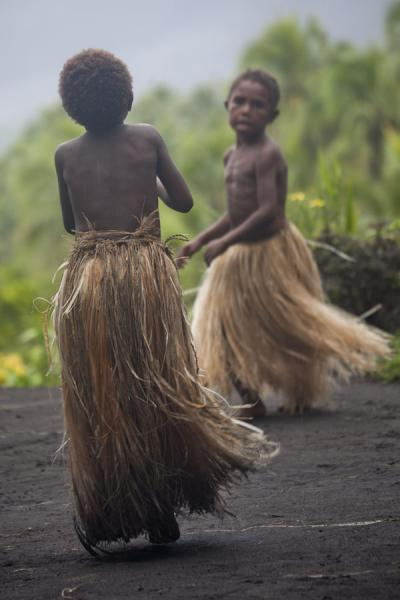 Picture of Tanna traditional village (Vanuatu): Kids with grass skirts dancing a traditional dance