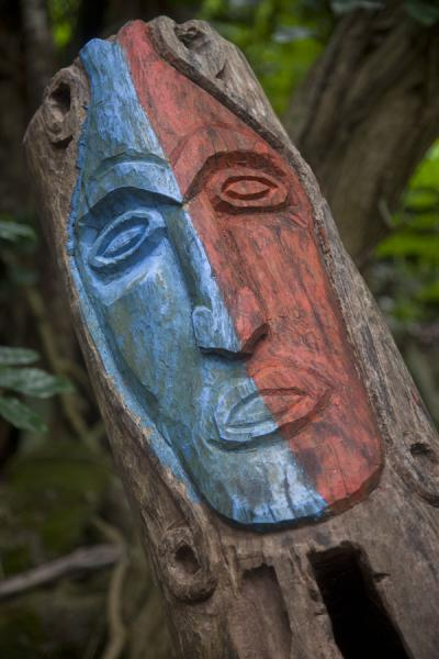 Foto van Close-up of the blue and red painted carved face on top of a tam-tam on the nasala of Wala IslandWala - St Vincent en de Grenadines