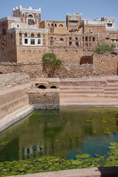 Some of the buildings reflected in the water cistern | Kawkaban | Yemen