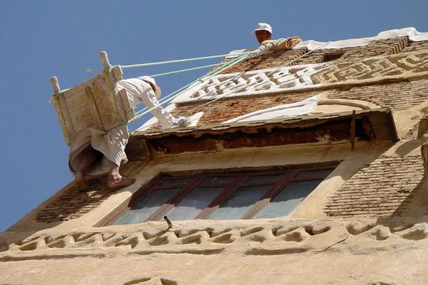 Picture of Old San'a (Yemen): Painter at work outside one of Old San'a's houses