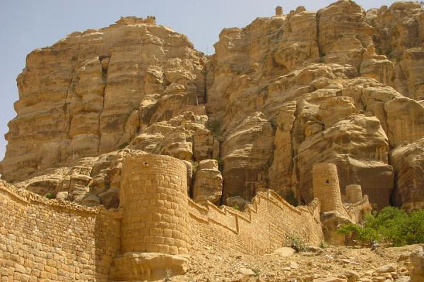 Foto di Part of the city wall of Thulla and the mountain towering above the townThulla - Yemen