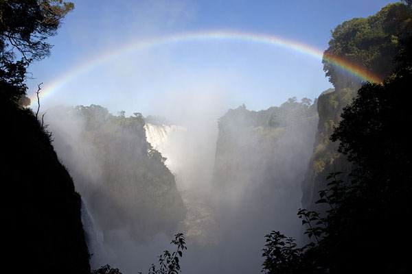 Foto van Rainbow spanning the gorge into which the Zambezi plunges: Victoria FallsVictoria Falls - Zimbabwe